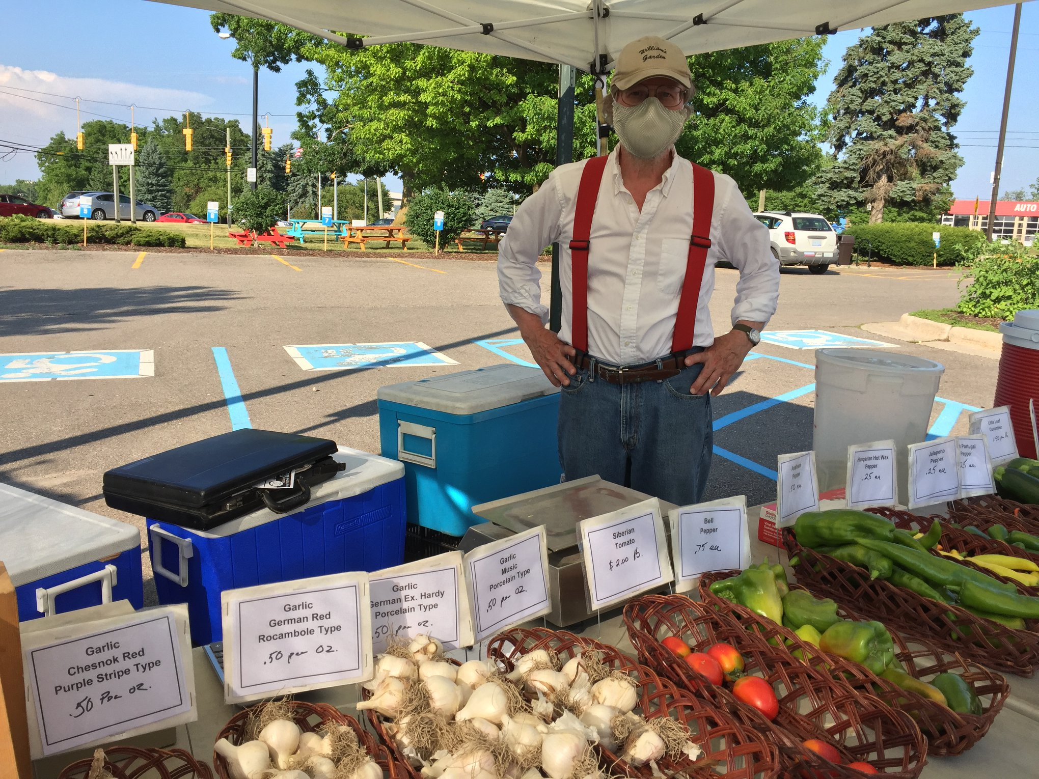 A farmer at the Westside Farmers' Market with garlic and tomatoes