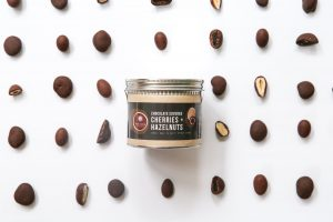 A can of Askinosie chocolate-covered hazelnuts and cherries, surrounded by the chocolate pieces.